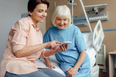 happy senior woman and daughter sitting on bed and using smartphone in hospital