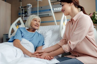 senior woman and daughter sitting on bed, looking at each other and holding hands in hospital