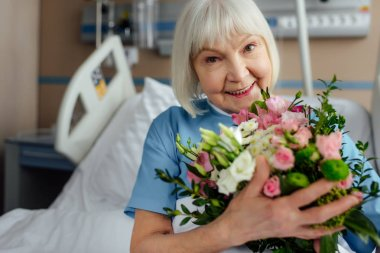 happy recovering senior woman on bed with flowers in hospital