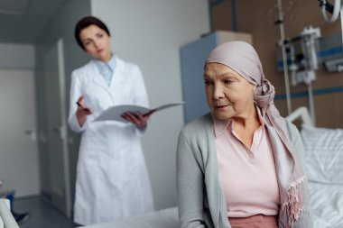 upset senior woman in kerchief with cancer sitting on hospital bed with female doctor holding diagnosis on background