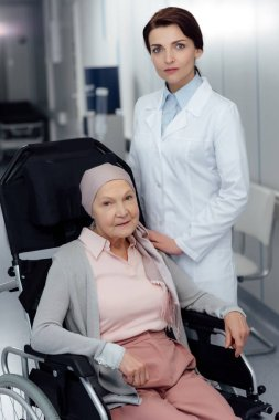 focused female doctor near senior woman in kerchief with cancer sitting in wheelchair in hospital