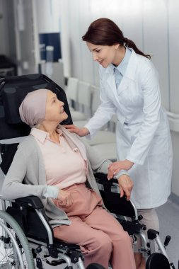 smiling female doctor near senior woman in kerchief with cancer sitting in wheelchair in hospital