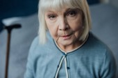 Fotografie portrait of sad senior woman with grey hair looking at camera at home
