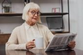 maggiore della donna con capelli grigi che si siede al tavolo e legge il giornale mentre beve il caffè a casa