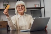 senior woman in glasses sitting at computer desk, holding credit card and doing online shopping at home