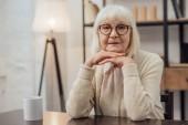 Starší žena sedí u stolu, opřel bradu rukama a při pohledu na fotoaparát doma