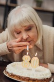 Fotografie ältere Frau aufleuchten Zigarette von brennenden Kerzen auf der Geburtstagstorte zu Hause
