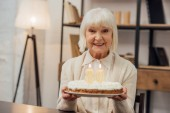 smiling senior woman holding cake with number 80 on top and celebrating birthday at home