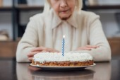 Photo cropped view of senior woman sitting at table and looking at birthday cake with burning candle at home