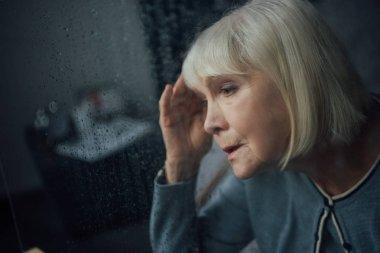 portrait of sad senior woman having headache at home through window with raindrops