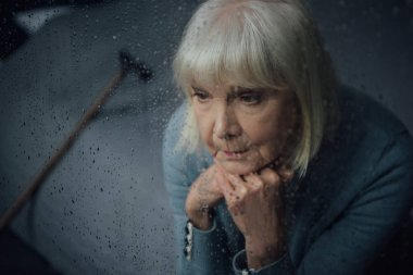 depressed senior woman sitting and propping chin with hands at home through window with raindrops