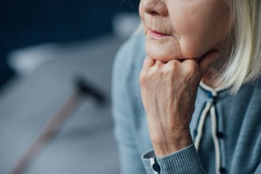 cropped view of senior woman propping chin with hand at home
