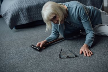 lonely senior woman lying on floor with walking stick and feeling unwell at home