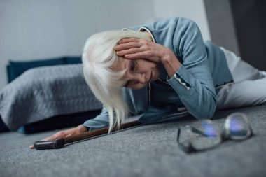 lonely senior woman lying on floor and having headache at home