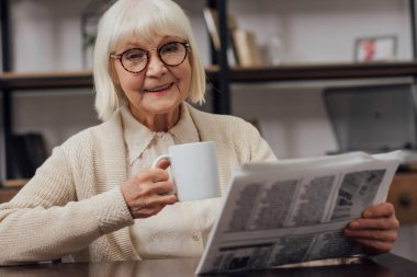 happy senior woman sitting at table and reading newspaper while drinking coffee at home