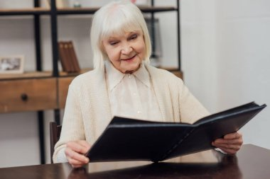 smiling senior woman with grey hair sitting at table and looking at photo album at home