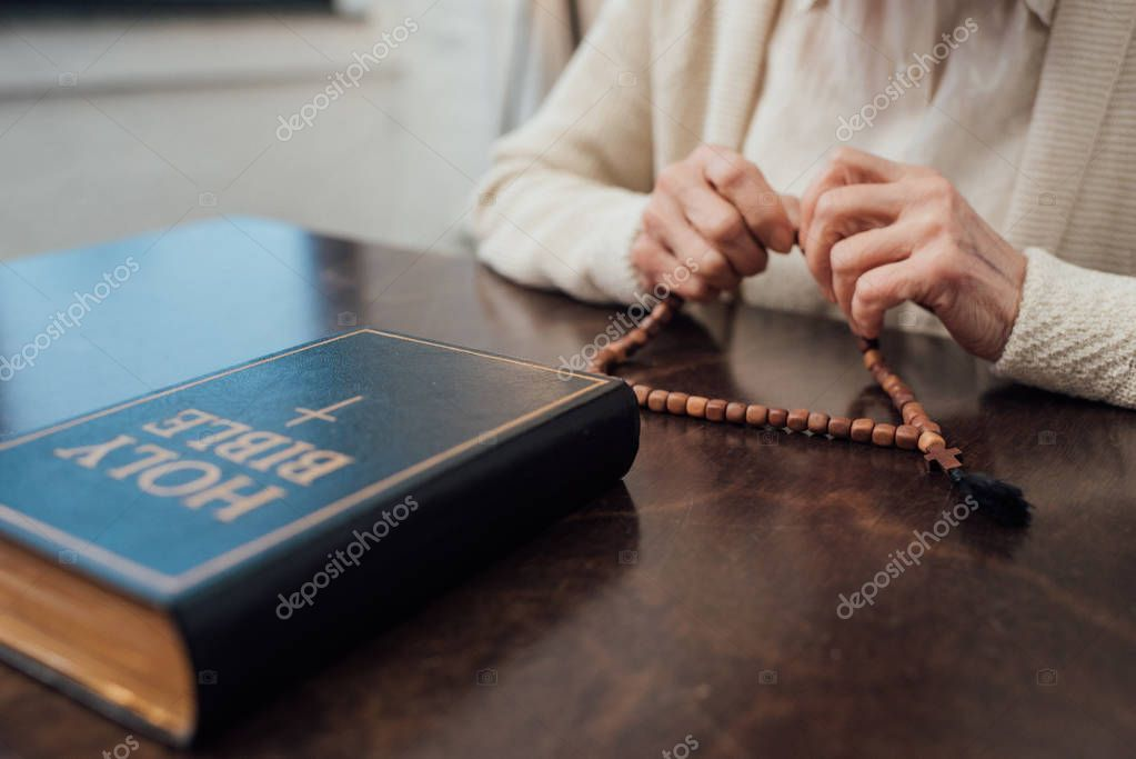 Partial view of senior woman sitting at table with rosary and holy bible at home stock vector