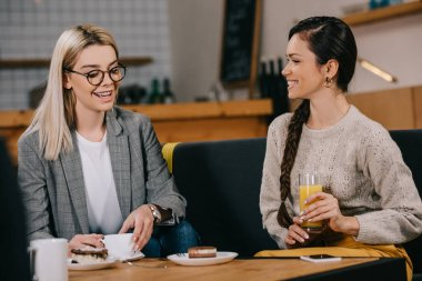attractive friends chatting in cafe with drinks