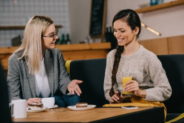 smiling woman chatting with friend while holding drink in cafe