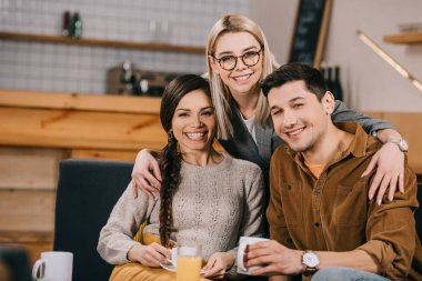 cheerful woman in glasses hugging smiling friends in cafe