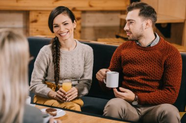 selective focus of handsome man looking at smiling woman in cafe