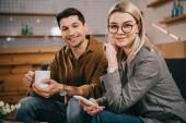 nő a gazdaság smartphone közelében kupa férfi szemüveg