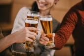 oříznutý pohled happy přátel cinkání s pivem