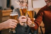 oříznutý pohled šťastné ženy, cinkání s pivo s přáteli