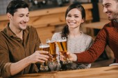 happy woman smiling near friends while clinking with beer