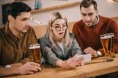 překvapený žena při pohledu na smartphone poblíž mužských přátel se sklenice piva