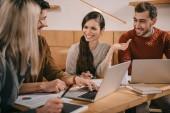 Fröhliche Gruppe von Mitarbeitern unterhält sich in Café in der Nähe von Laptops