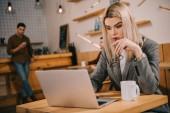 Fotografia messa a fuoco selettiva della donna premurosa che esamina computer portatile nella caffetteria