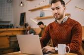 jóképű férfi nézett fényképezőgép, rövid idő használ a laptop a kávézóban
