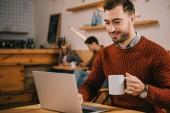 vidám ember látszó-on laptop-miközben kávét a café