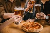 Fotografie oříznutý pohled přátel opékání sklenic piva v barech