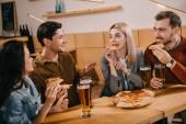cheerful woman eating pizza near friends in bar