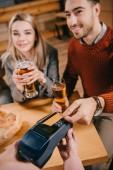 Fotografie Selektivní fokus člověka platit kreditní kartou zároveň pokladní terminál v rukou drží