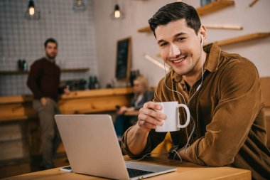 handsome man in earphones holding cup of coffee near laptop in cafe