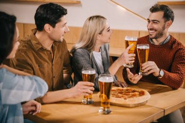 selective focus of cheerful friends toasting glasses of beer in bar