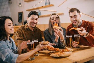 happy woman eating pizza near friends in bar