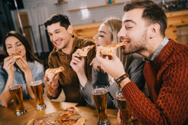 Selective focus of happy friends eating pizza in bar stock vector