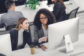 pohled z vysokého úhlu úsměvu mnohonárodnostní podnikatelky pomocí stolního počítače v kanceláři