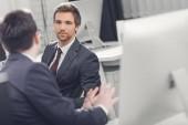 Selektivní fokus obchodníků mluvit když spoli pracovali v kanceláři