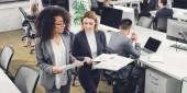 vysoký úhel pohled mladých mnohonárodnostní podnikatelky držitelům dokladů a diskusi o projektu při chůzi v úřadu