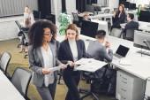 Fényképek magas szög kilátás szakmai fiatal többnemzetiségű üzletasszonyok gazdaság dokumentumokat, és megvitatni a projekt iroda