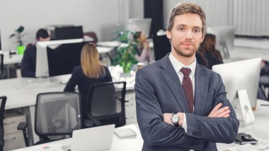 handsome confident young businessman standing with crossed arms and looking at camera in office