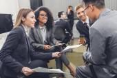 Fényképek mosolygó fiatal többnemzetiségű üzletemberek gazdaság dokumentumokat, és megvitatni a projekt iroda
