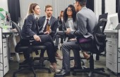 Fotografie profesionální mladých mnohonárodnostní obchodní tým v formální oblečení sedí pohromadě a diskutovat o práci v kanceláři