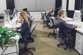 boční pohled na profesionální mladí podnikatelé v práci se stolními počítači v kanceláři formální oblečení
