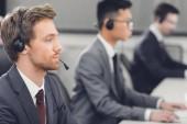Fotografie boční pohled soustředěný mladý podnikatel v headsetu, spolupráce s kolegy v call-centru